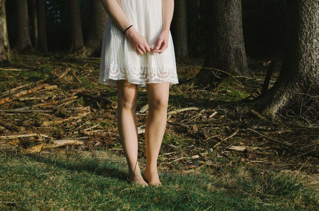 素足と手をさらしたワンピースを着た女性