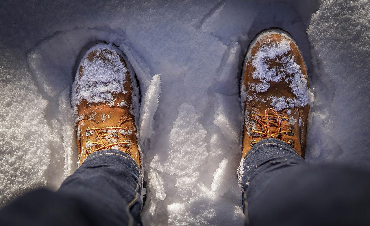 雪の中でブーツを履いている人
