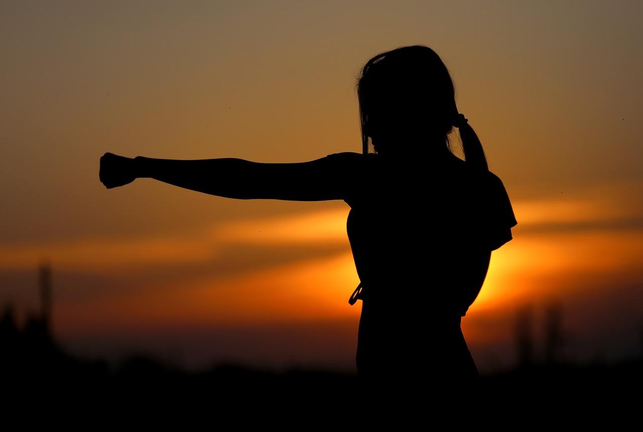 夕焼けを背景にパンチする女性